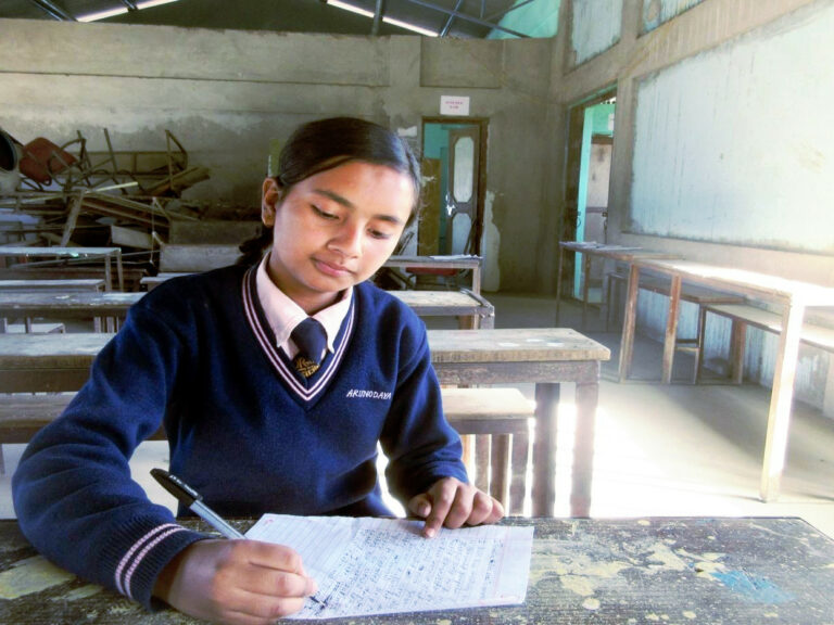 una ragazza nepalese seduta nella sua classe