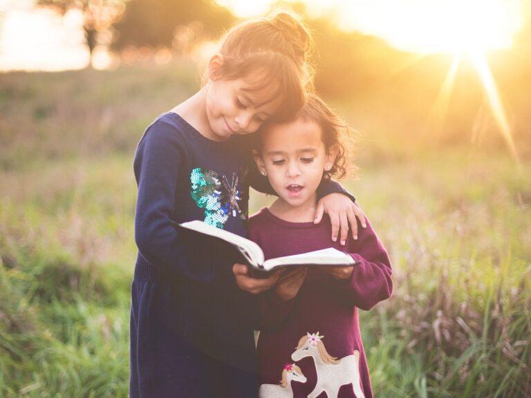 Due sorelle leggono un libro per bambini