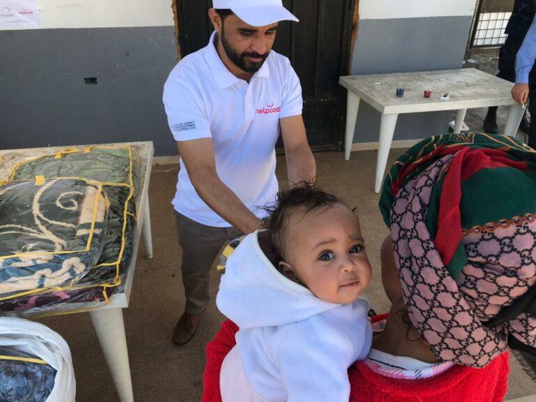 una mamma e la sua bambina ricevono coperte in un centro libico